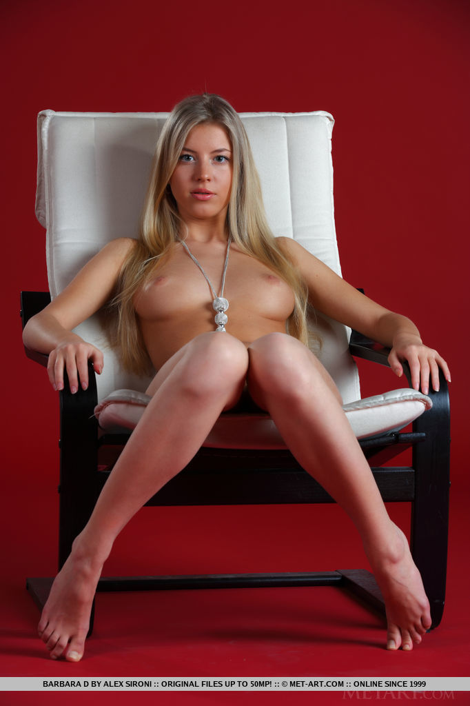 Barbara D sitting nude on the armchair
